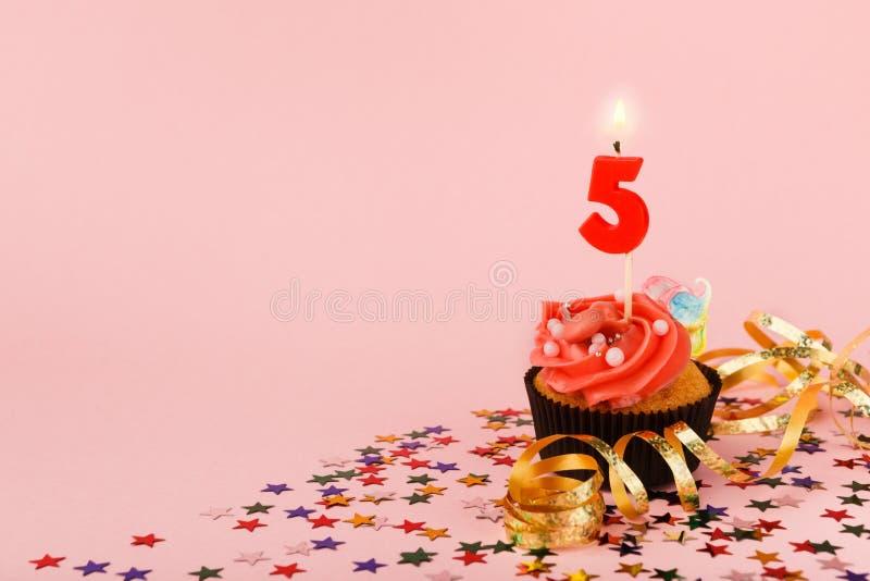 Le cinquième petit gâteau d'anniversaire avec la bougie et arrose images libres de droits