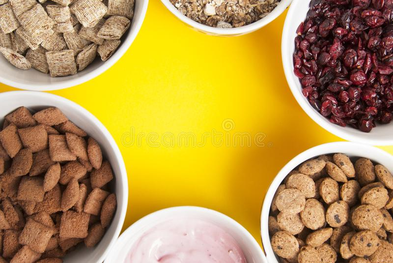 Le ciotole di interi muesli del grano, di frutti secchi, di granola e di oatmeals hanno sistemato nel cerchio con lo spazio della fotografia stock libera da diritti