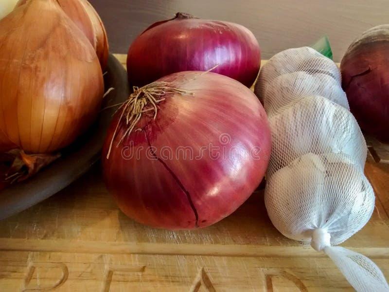Le cipolle bianche e porpora ed i chiodi di garofano di aglio sopra woden il tagliere immagine stock