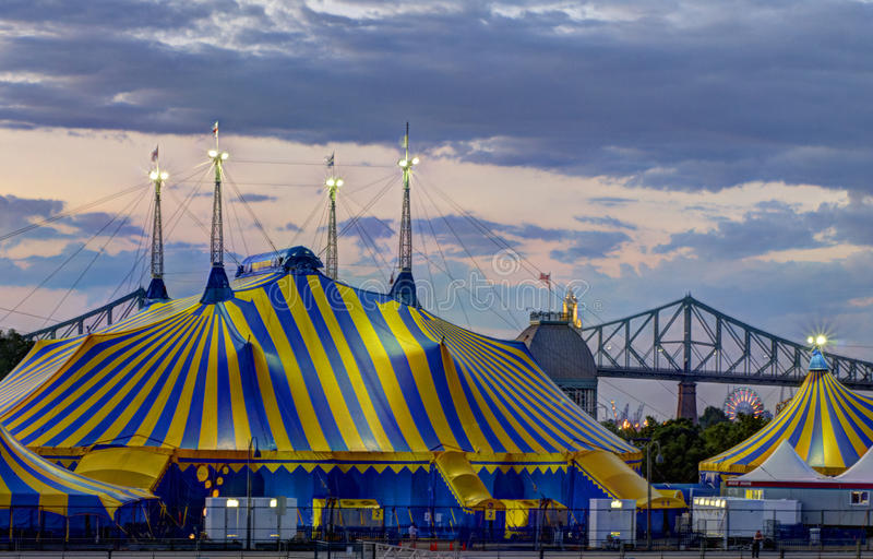Le Cirque is in town. Tents of Le Cirque du Soleil in Old Port of Montreal, with the Jacques Cartier Bridge and the Ferris Wheel from LaRonde in the background royalty free stock images