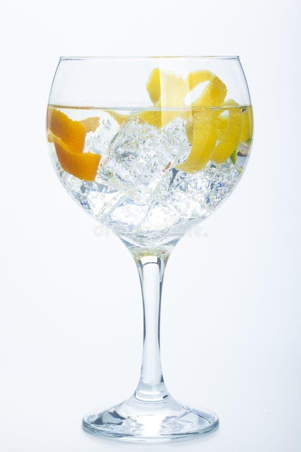 Le citron et la chaux oranges égrènent le tonique au-dessus du blanc photos stock
