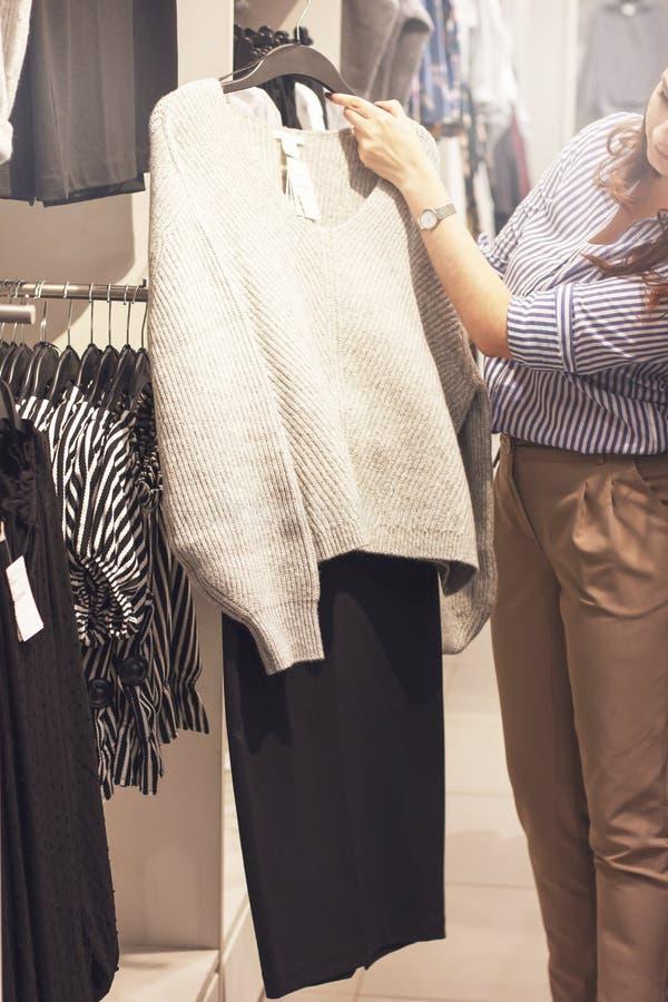 Le client de styliste de jeune femme choisit des vêtements dans le magasin photographie stock