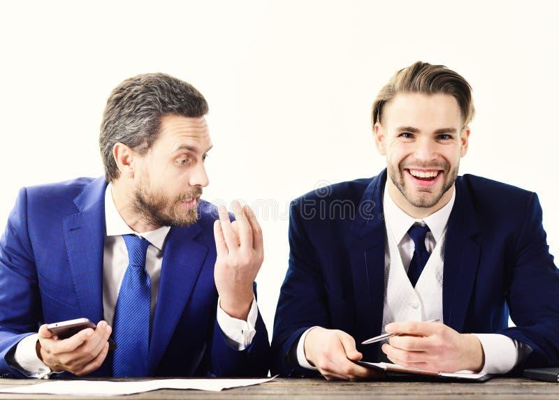 Le client heureux signe le contrat avec l'agent immobilier Vrai agent immobilier et jeune homme d'affaires avec le visage de sour image libre de droits
