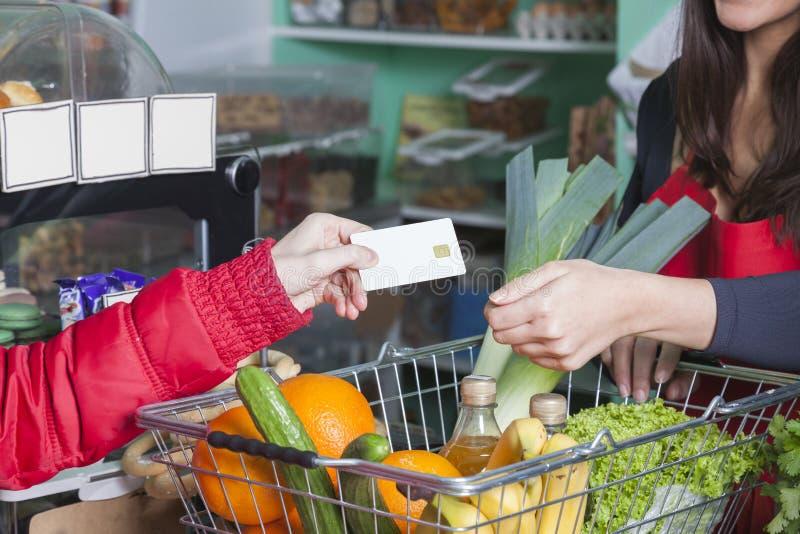 Le client paye avec la carte de crédit en épicerie images libres de droits