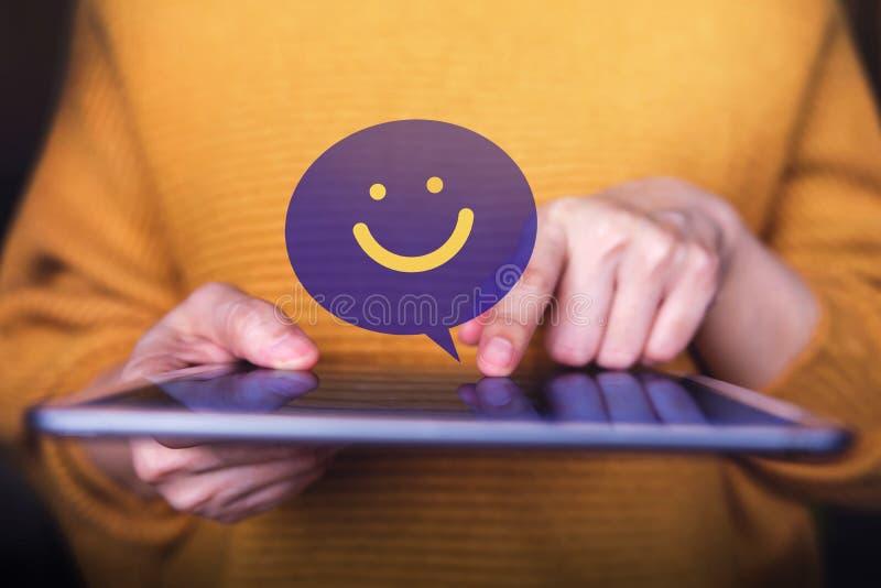 Le client ?prouve le concept Client heureux à l'aide de la Tablette de Digital à envoyer un examen positif photos libres de droits