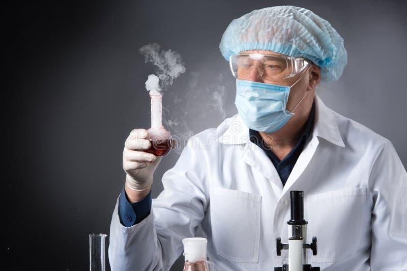 Le clinicien sérieux étudie avec des outils dans le laboratoire et flacon de se tenir photographie stock