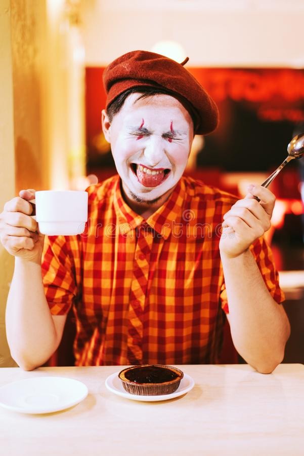 Le clown mange un gâteau dans un café et son visage coasse image stock