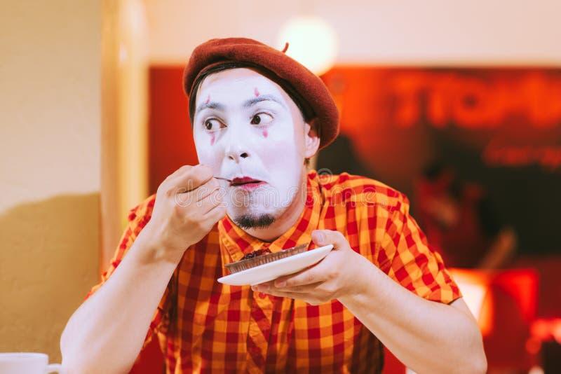 Le clown mange un gâteau dans un café et son visage coasse photo stock