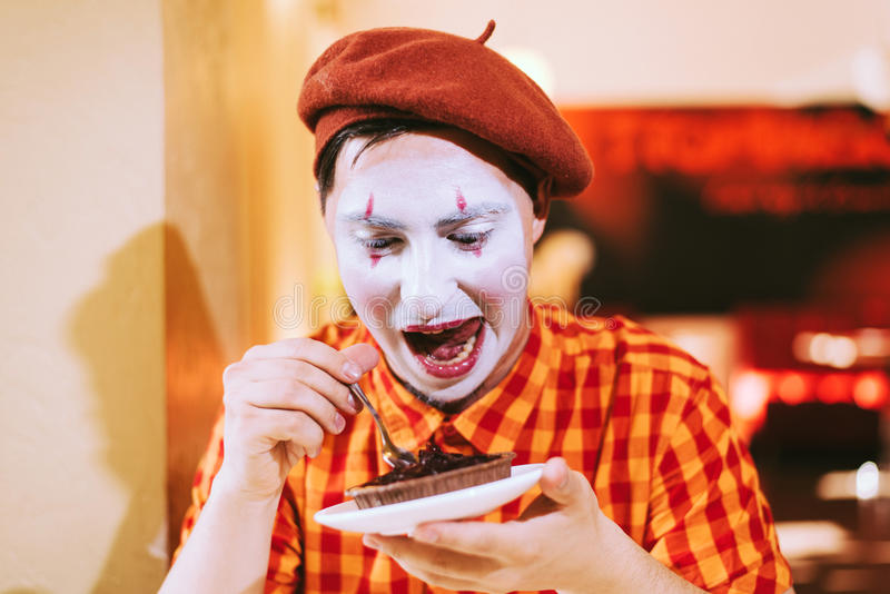 Le clown mange un gâteau dans un café et son visage coasse photos stock