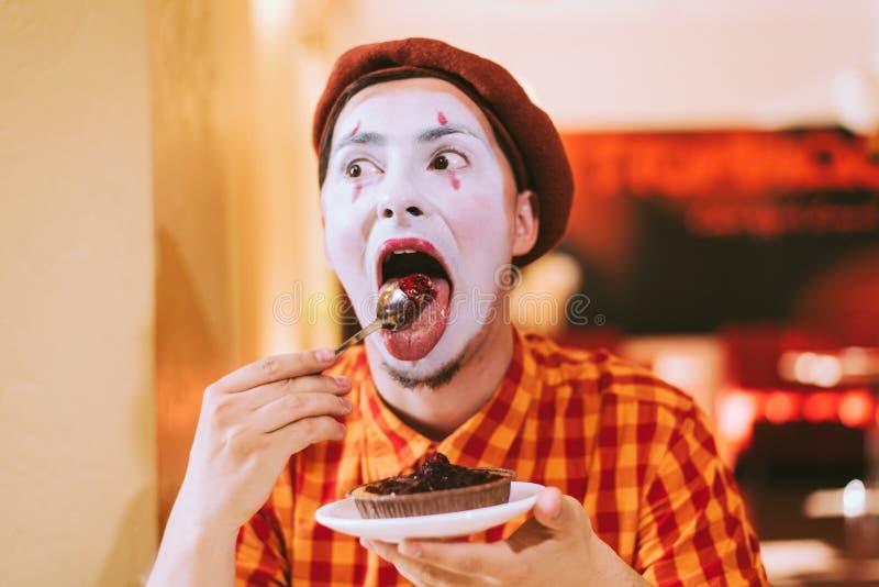 Le clown mange un gâteau dans un café et son visage coasse photos libres de droits