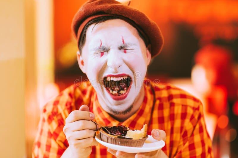 Le clown mange un gâteau dans un café et son visage coasse images libres de droits