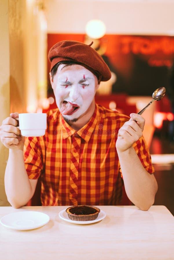 Le clown mange un gâteau dans un café et son visage coasse images stock
