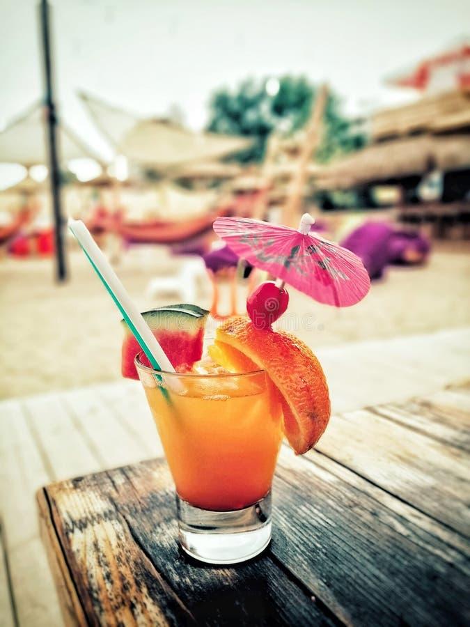 Le cocktail sur la boisson d'Oranjeco de plage a régénéré image libre de droits
