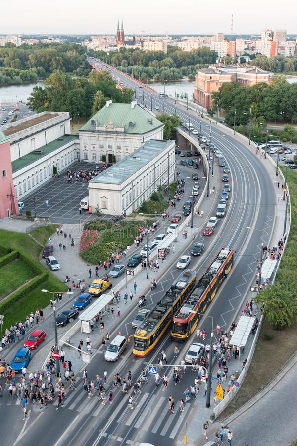 Le code delle automobili si formano come più dei tram dell'uscita di cento genti ed attraversano la strada alla fermata del tram  immagini stock