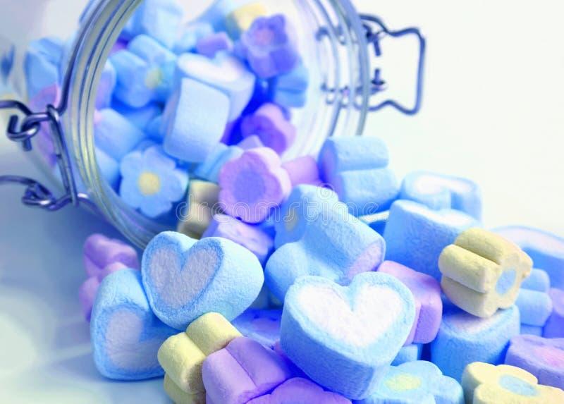 Le coeur bleu et pourpre en pastel de couleur et fleurissent les sucreries formées de guimauve dispersées du pot en verre sur le  photographie stock libre de droits