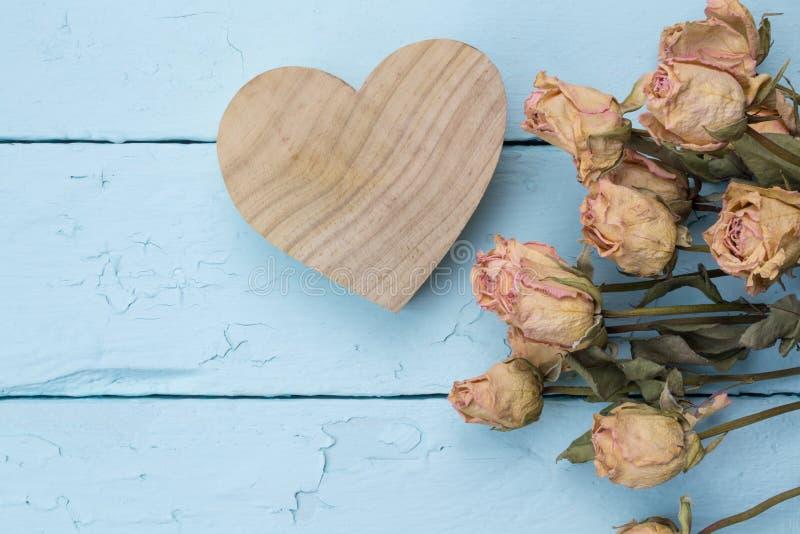 Le coeur découpé par bois naturel avec les roses roses sèches se ferment sur le bleu images stock