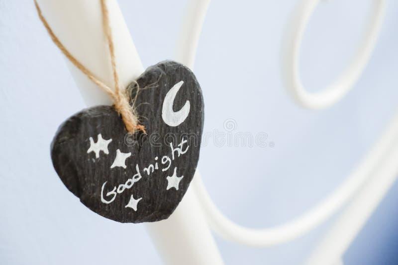 Le coeur de l'ardoise accroche comme décoration sur un lit de cadre en acier avec bonne nuit écrit là-dessus photo libre de droits