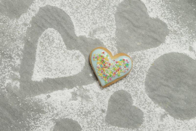 Le coeur de la valentine cuite au four couvert de glaçage et de confettis bleus photo stock