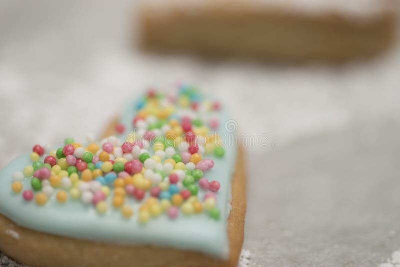 Le coeur de la valentine cuite au four couvert de glaçage et de confettis bleus images libres de droits