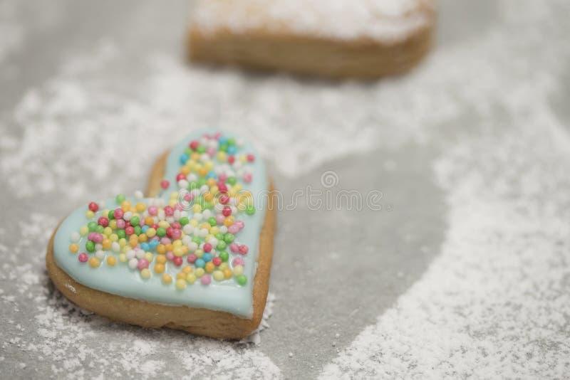 Le coeur de la valentine cuite au four couvert de glaçage et de confettis bleus image stock