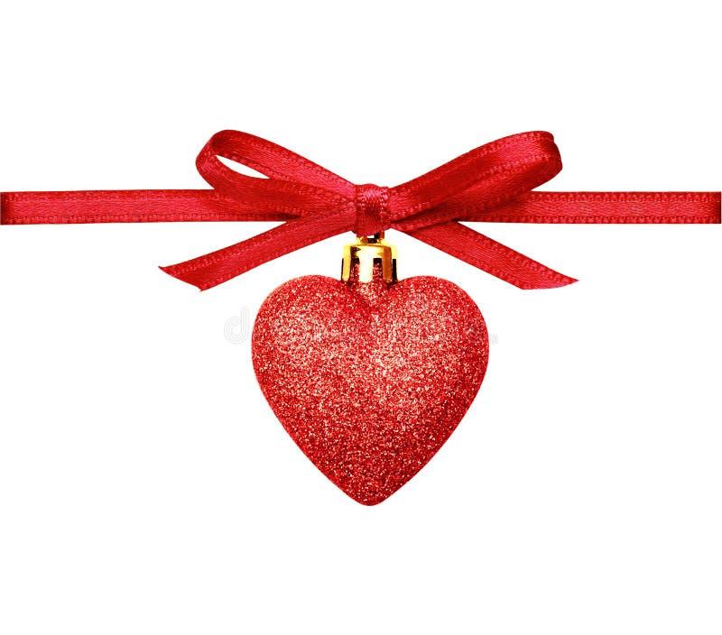 Le coeur de scintillement de Noël et le ruban rouges de soie cintrent photographie stock libre de droits