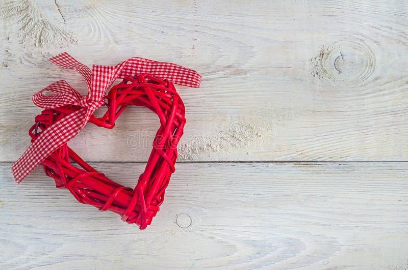 Le coeur en osier rouge sur la copie en bois rustique blanche de Th de fond a épargné le coeur en osier sur le fond en bois rusti photo libre de droits
