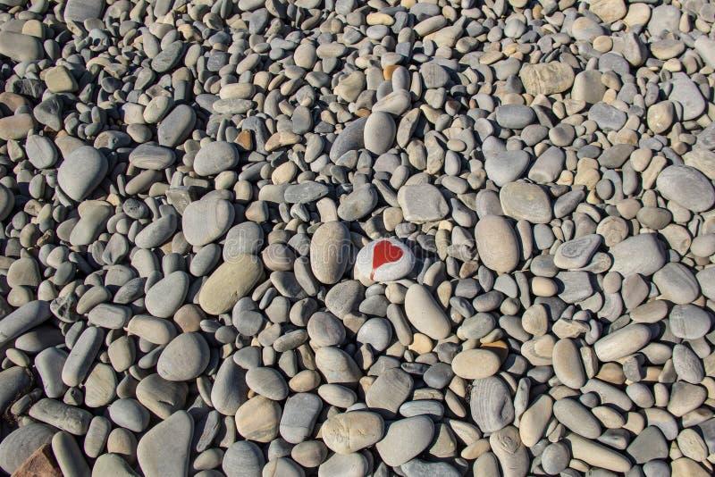 le coeur en pierre a peint avec un marqueur rouge de peinture sur le caillou comme cadeau pour le Saint Valentin de saint sur le  images stock