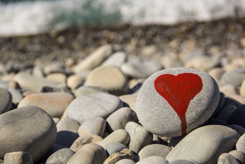 le coeur en pierre a peint avec un marqueur rouge de peinture sur le caillou comme cadeau pour le Saint Valentin de saint sur le  photographie stock libre de droits