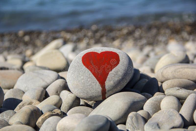 le coeur en pierre a peint avec un marqueur rouge de peinture sur le caillou comme cadeau pour le Saint Valentin de saint sur le  photo libre de droits