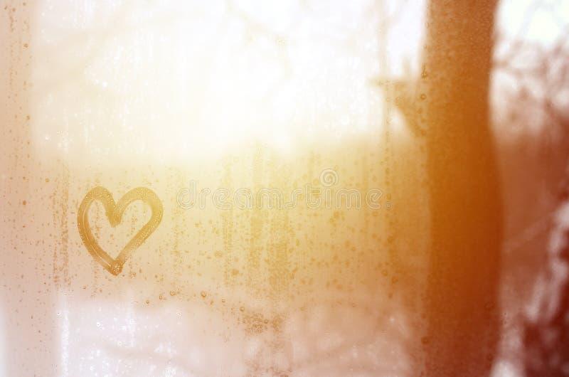 Le coeur est peint sur le verre misted pendant l'hiver image stock