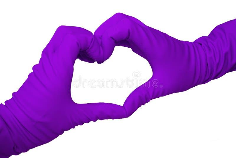 Le coeur a fait par deux mains dans des gants de latex sur le blanc photo libre de droits