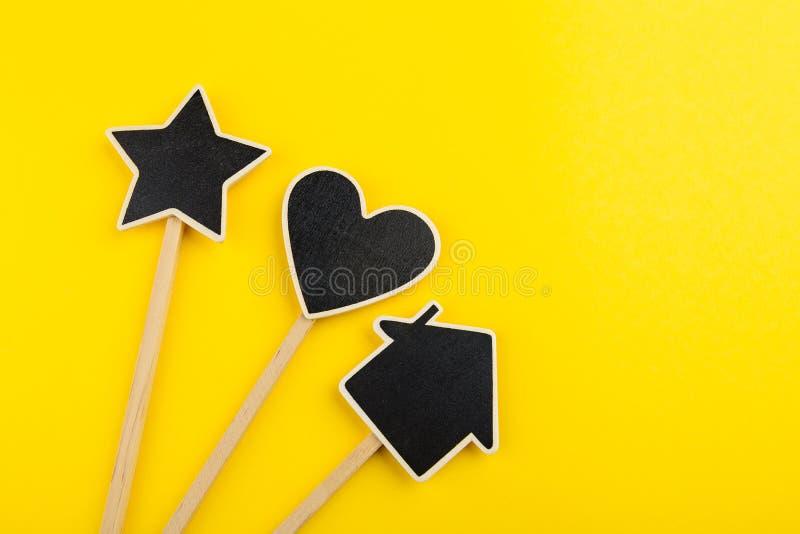 Le coeur, l'étoile et la maison noirs de tableau forment sur un bâton en bois photo stock