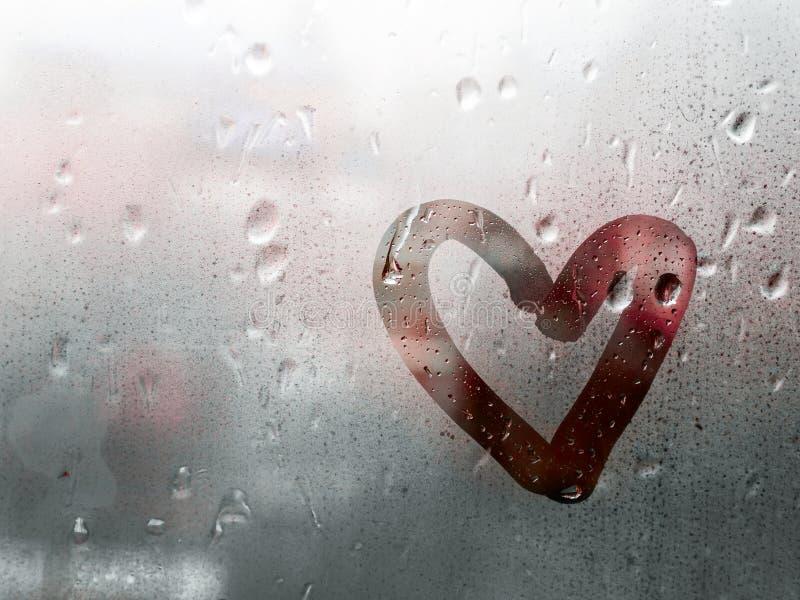 Le coeur a peint sur le verre est embrumé et il y a beaucoup de baisses là-dessus photographie stock