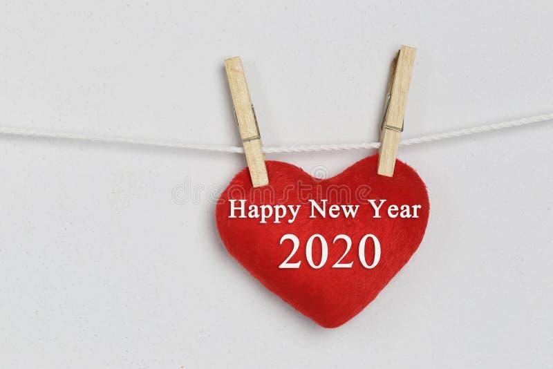 Le coeur rouge accrochant sur une corde et ont le texte de bonne année photographie stock libre de droits