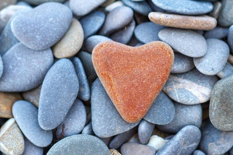 Le coeur rouge en pierre se trouve sur le concept de caillou de l'amour image stock