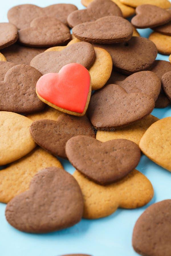 Le coeur rouge a fait du pain d'épice vitré au-dessus d'un groupe de biscuits image libre de droits