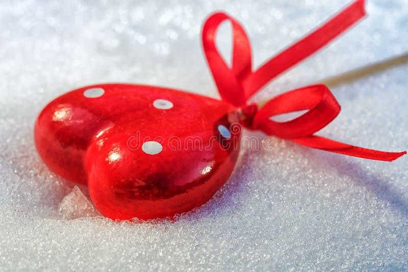 Le coeur rouge sur la neige humide de glace fond, foyer sélectif photographie stock