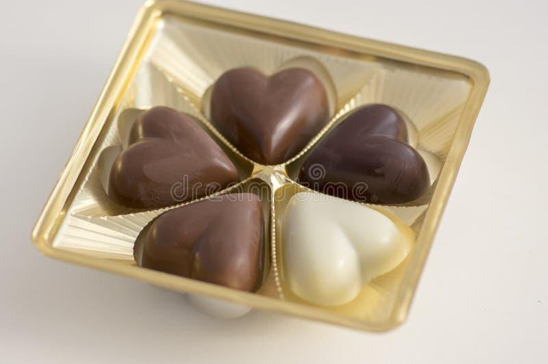 Le coeur shapped la couleur de bonbons à chocolat, brune et blanche, boîte en plastique transparente avec des pralines images stock
