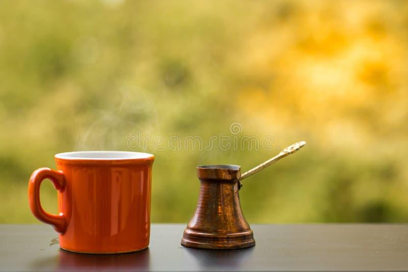 Le coffe savoureux chaud dans la tasse rouge a brassé dans un pot traditionnel de café turc, table de café dehors photographie stock libre de droits