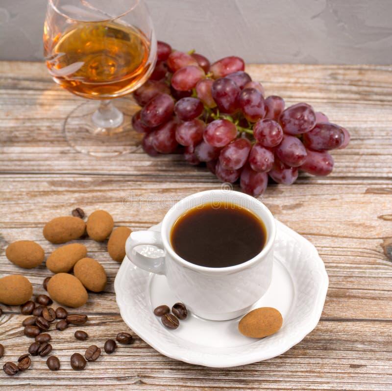 Le coffie et le verre noirs avec l'eau-de-vie fine ont servi avec du raisin et le chocola photos stock
