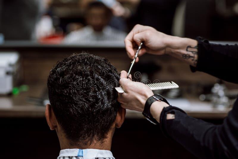 Le coiffeur coupe les cheveux d'un homme tenant des ciseaux et les peigne dans des ses mains vis-à-vis du miroir dans un raseur-c photos libres de droits