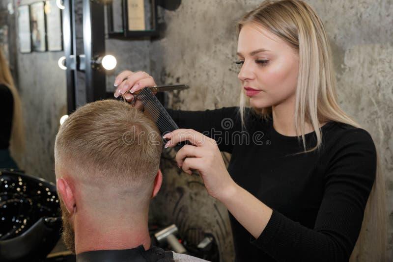 Le coiffeur coupe les cheveux du client dans le salon de coiffure photo stock