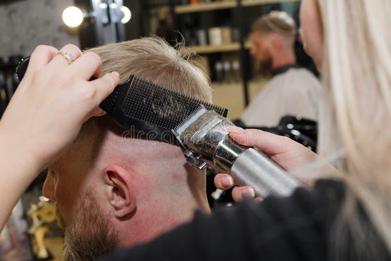 Le coiffeur coupe les cheveux du client dans le salon de coiffure photographie stock libre de droits