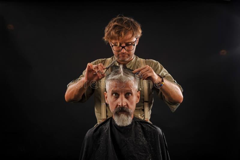 Le coiffeur coupe le vieillard avec une barbe sur un fond foncé image libre de droits