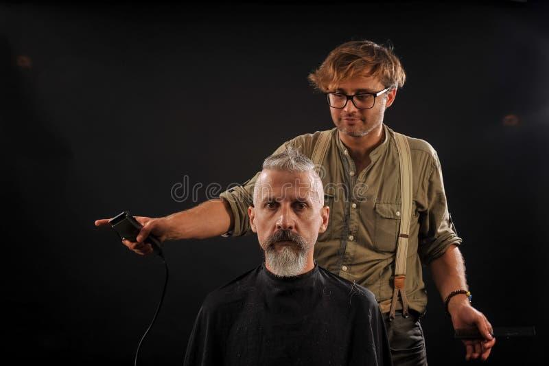 Le coiffeur coupe le vieillard avec une barbe sur un fond foncé photo libre de droits
