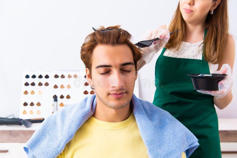 Le coiffeur de femme appliquant le colorant pour équiper des cheveux photo libre de droits