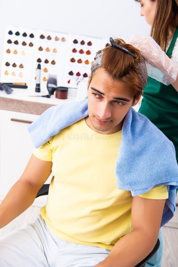 Le coiffeur de femme appliquant le colorant pour équiper des cheveux image stock