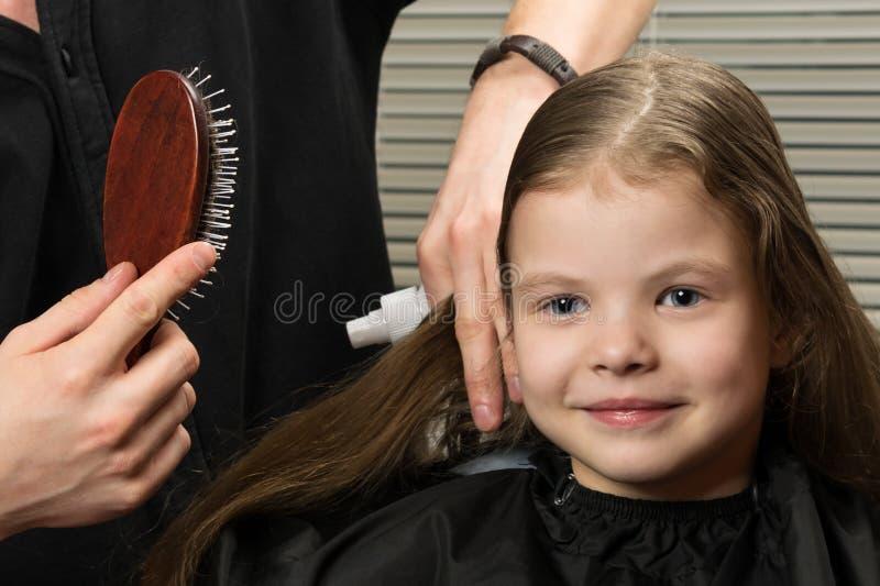 Le coiffeur de styliste peigne de longs cheveux de fille dans le salon de beauté image libre de droits
