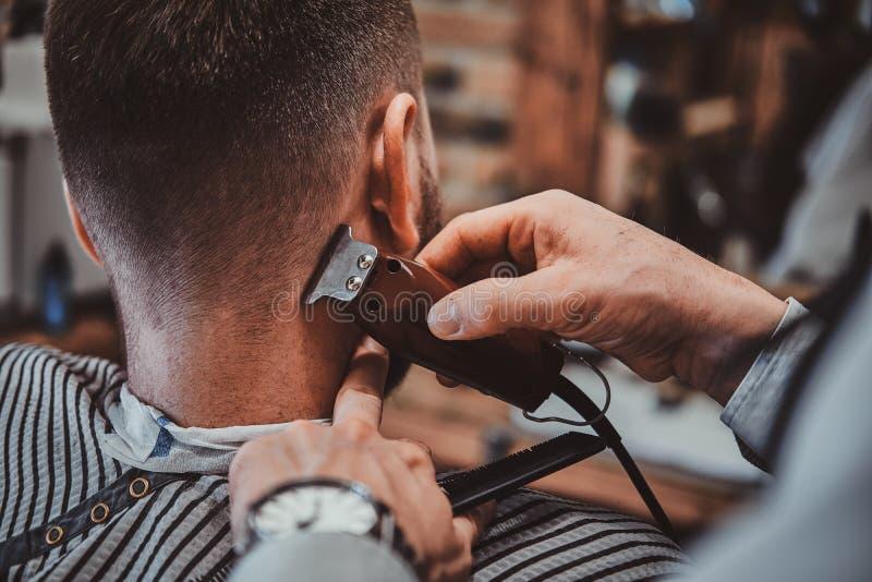 Le coiffeur de Thendy au raseur-coiffeur moderne travaille à la coupe de cheveux du client images libres de droits