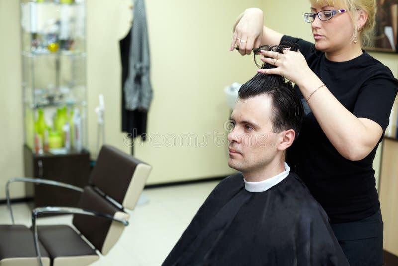 Le coiffeur féminin coupe le cheveu d'homme photo libre de droits